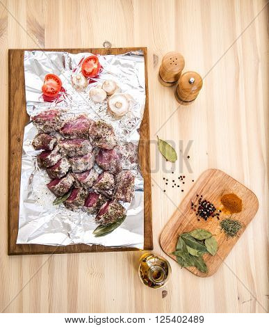 Fresh meat in marinade and spices ready to cook. Food background.