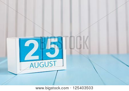 August 25th. Image of august 25 wooden color calendar on blue background. Summer day. Empty space for text.