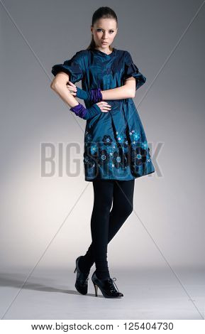 Full body fashion model in fashion dress posing in light background