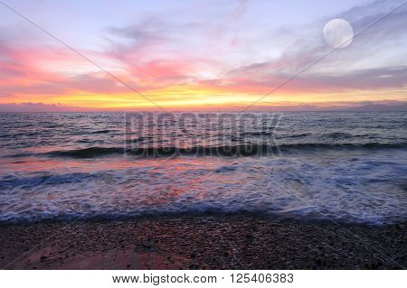 Ocean sunset is brightly lightred and golden seascape with a gentle wave rolling to the shore and a full moon rising in the sky.