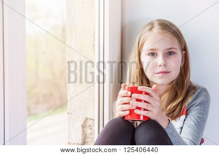 Little beauty girl sitting twith cup at the window ** Note: Soft Focus at 100%, best at smaller sizes