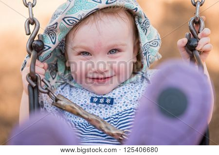 Young girl wearing a hat and swinging on a swing is smiling and her blue eyes are looking into the camera.  She is smiling and her feet are blurred in the foreground.