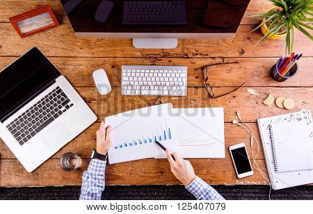 Business person at the office desk working with chart graph. Smart phone, notebook, notepad and eyeglasses and various office supplies around the workplace. Flat lay.