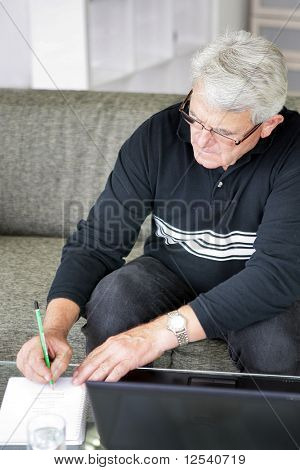 Portrait of a senior man writing on a document