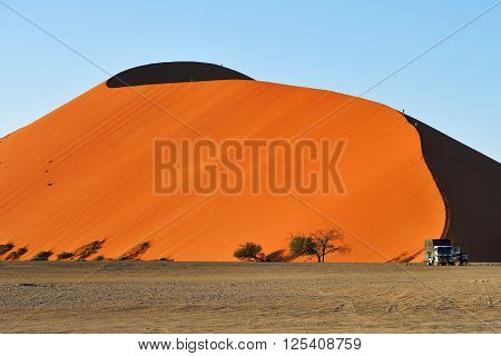 SOSSUSVLEI NAMIBIA - JAN 29 2016: Tourists climb Dune No.45 at sunrise most popular dune in the whole World Namibia Africa