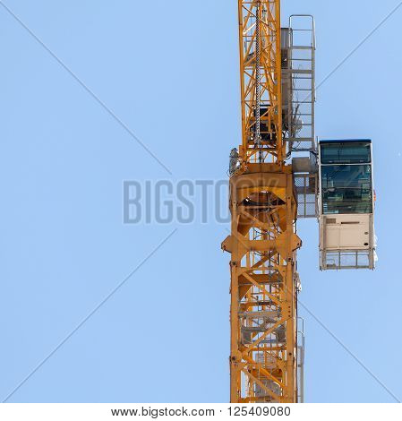 Fragment of yellow hoisting crane with cab on  blue sky background.