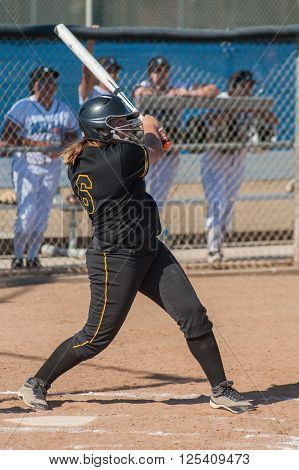 Strong softball player in black uniform watching her hit ball fly.
