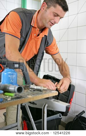 Portrait of a man with a blowtorch and a toolbox