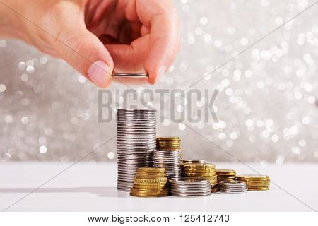 Man's hand puts coins in a stacks. Money growth concept. Festive silver background with sparkles.