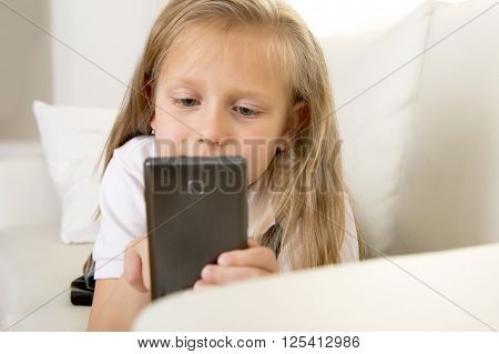 sweet cute and beautiful 6 or 7 years old female child with blond hair in school uniform sitting on home sofa couch using internet app on mobile phone playing online game looking happy and relaxed