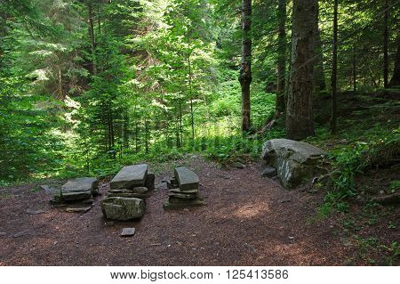 Rest place from stones in the forest.
