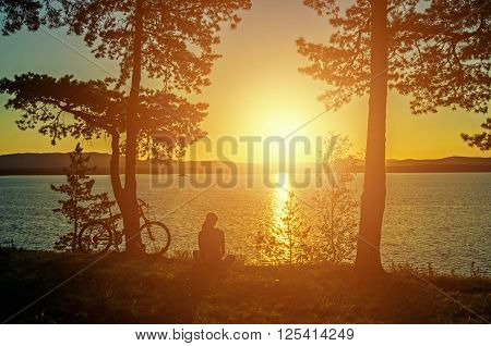 Summer silhouette landscape - unidentified tourist girl with bicycle at the edge of the cliff looking the sun setting behind the mountains on Irtyash Lake in Southern Urals Russia
