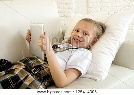 sweet cute and beautiful 6 or 7 years old female child with blond hair in school uniform lying on home sofa couch using internet app on digital tablet pad playing online game smiling happy