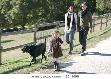 A family having a walk with a dog