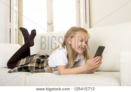 sweet cute and beautiful 6 or 7 years old female child with blond hair in school uniform lying on home sofa couch using internet app on mobile phone playing online game looking happy and relaxed