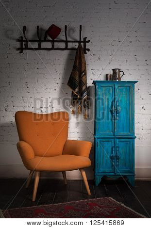 Composition of vintage orange armchair blue cupboard wall hanger with ornate scarf and red fez in studio
