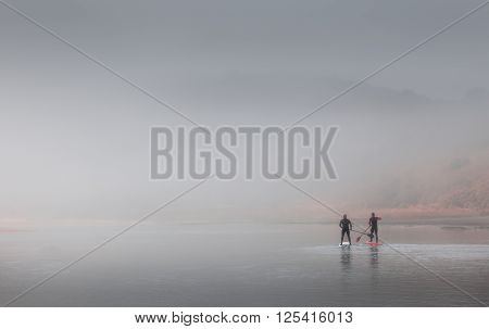 Swansea, UK - April 12, 2016: Two men choose to keep fit by paddleboarding in heavy misty conditions on the river at Three Cliffs Bay, Gower
