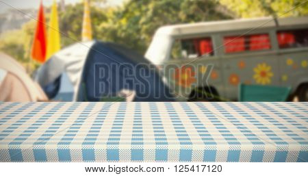 Part of blue and white tablecloth against empty campsite at music festival