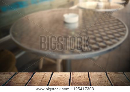 Wooden desk against bar stool and table with ash tray