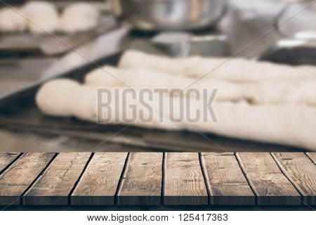 Wooden table against worktop with dough and bread uncooked