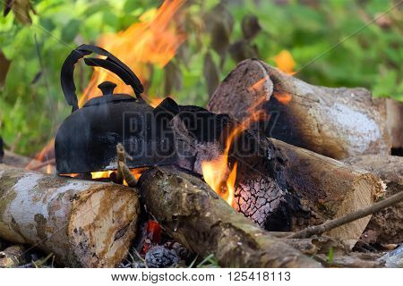 Boiling water in burnt kettle on wild campfire