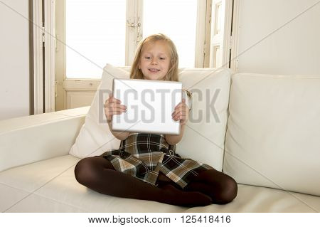 sweet cute and beautiful 6 or 7 years old female child with blond hair in school uniform sitting on home sofa couch using internet app holding digital tablet pad playing online game smiling happy