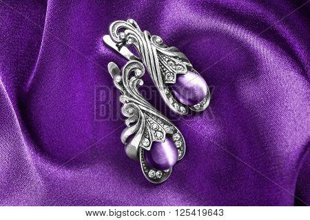 Vintage amethyst earrings on purple satin as a background