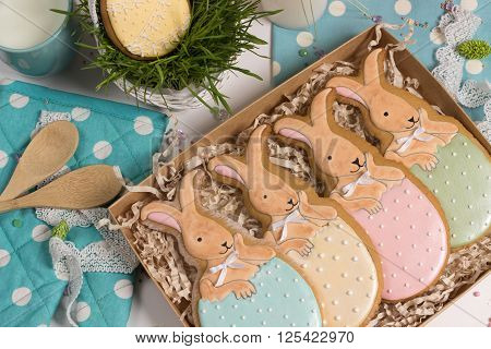 family holiday present box with nice sweet multicolored trendy easter rabbits honey-cake on kithen with wooden spoons food photo