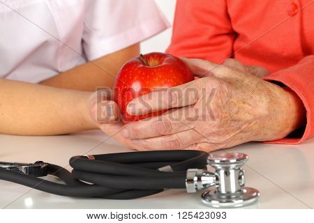 Caregiver touching elderly patients hand at home