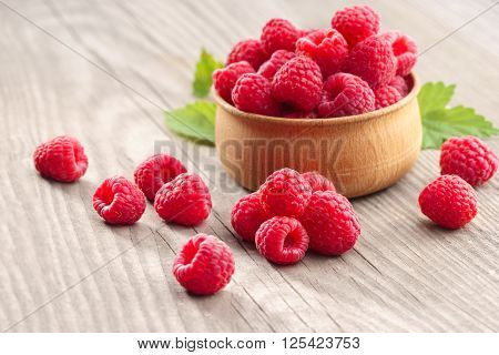Deluxe Raspberries in bowl on wooden table. Close up high resolution product. Harvest Concept