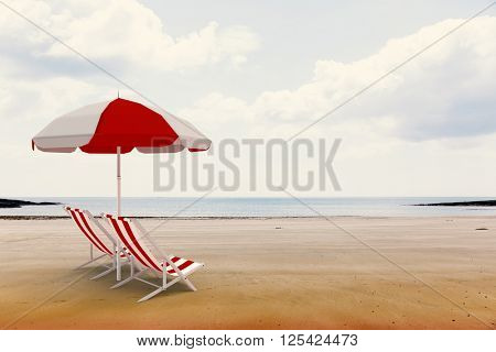 Image of sun lounger and sunshade against beach