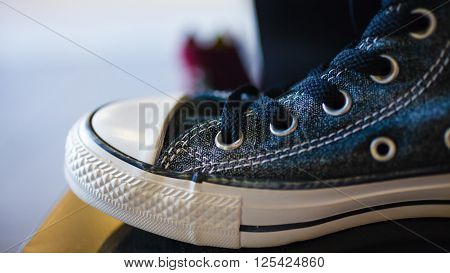 Sport fashion. Closeup navy blue fashionable sneakers on shop shelf
