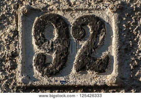 Old retro weathered cast iron plate with number 92