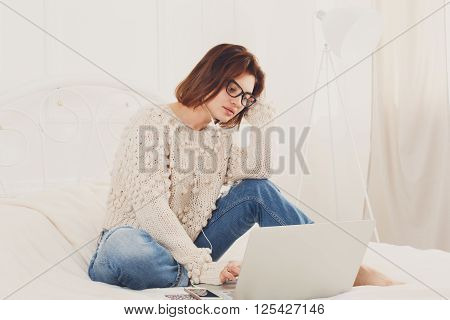 Young woman reads from laptop computer in bed. Engrossed Girl in eyeglasses and earphones with mobile phone. Attractive woman in casual clothes at white bed. Internet freelancer. High key, soft tone