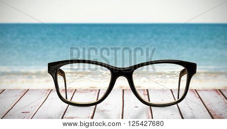 Reading glasses against a picture of a beach