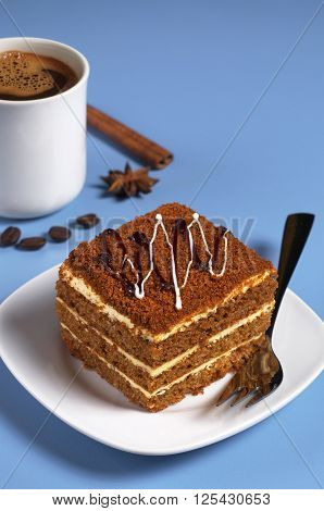 Honey cake and cup of coffee on a blue table