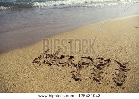 Word happy handwritten in sand on the beach next to the waterline