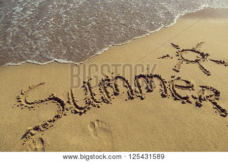 Word summer handwritten in sand on the beach next to the waterline