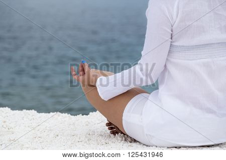 Young woman practicing yoga near marble beach on Thassos island Greece on a cloudy summer day