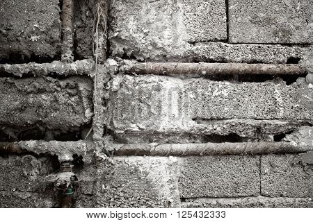 Raw concrete brick wall and water pipe on it background