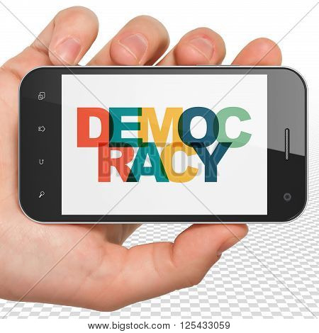 Politics concept: Hand Holding Smartphone with Democracy on  display