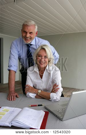 Portrait of a smiling senior couple in front of a laptop computer