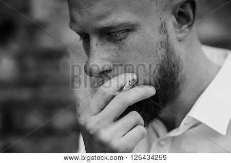 portrait of smoking young red hair man with beard black and white horizontal