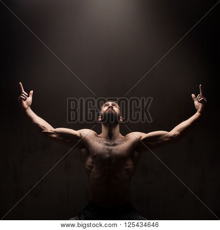 Man praying on dark studio background. Dramatic light from above
