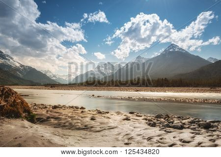 rural river water at alpine mountains in austria with clouds