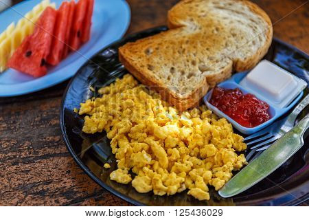Breakfast with scrambled eggs, toast and jam in cafe