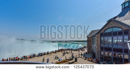 Niagara Falls, Ontario, Canada,  May 9th, 2015.  Summer-like weather draws locals, travellers, and tourists alike.  People of all ages gather along the fence to watch in awe the mighty Niagara Falls.