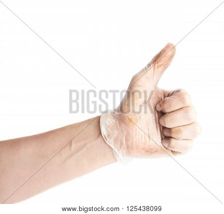 Worker's hand in a covered with dirt rubber glove thumbs up sign, composition isolated over the white background