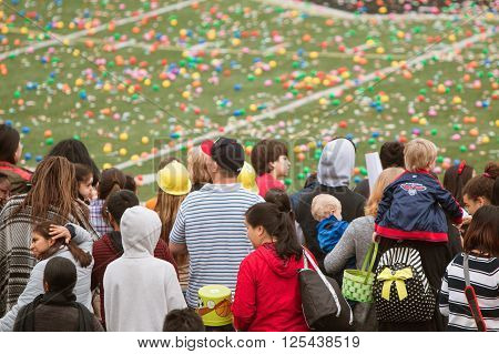 MARIETTA, GA - MARCH 2016: Children and families stand waiting for the start of a massive community Easter egg hunt on a local high school football field in Marietta GA on March 26 2016.