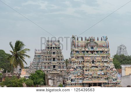 Trichy India - October 15 2013: Five gopurams of the temple in one shot. Four pastel colored with plenty of statues including the main Ranganathar depiction of Vishnu resting on the snake. The dirty-white Vellai Gopuram stands in the back.